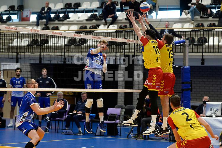 18-04-2021: Volleybal: Amysoft Lycurgus v Draisma Dynamo: Groningen, Lycurgus speler Bennie Tuinstra slaat de bal over het blok met Dynamo speler Maikel van Zeist en Dynamo speler Sjoerd Hoogendoorn