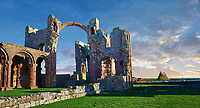 The Anglo Saxon Romanesque Lindisfarne Abbey ruins looking to Lidisfarne Castle,  Holy Island, Lindisfarne, Northumbria, England