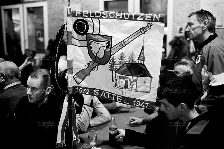 """Switzerland. Canton Zug. Morgarten. The group of men are members of the riflemen's association """"Felsdchützen Sattel"""". On their flag are drawn a target, a saddle, a rifle and a christian church. The men wait for the results of the Morgartenschiessen (Morgarten shooting) competition. Thousands competitors from all over Switzerland came to fire fifteen shots at targets arranged on a meadow. The Battle of Morgarten occurred on 15 November 1315, when a 1,500-strong force from the Swiss Confederacy ambushed a group of Austrian soldiers of the Holy Roman Empire on the shores of Lake Ägeri near the Morgarten Pass. The Swiss, led by Werner Stauffacher, defeated the Austrians, who were under the command of Duke Leopold I. The Swiss victory consolidated the Everlasting League of the Three Forest Cantons, which formed the core of modern Switzerland. The victory of the Confederates left them in their virtual autonomy. Morgarten is a Swiss village which belongs to the municipality of Oberägeri in the canton of Zug. 15.11.2017 © 2017 Didier Ruef"""