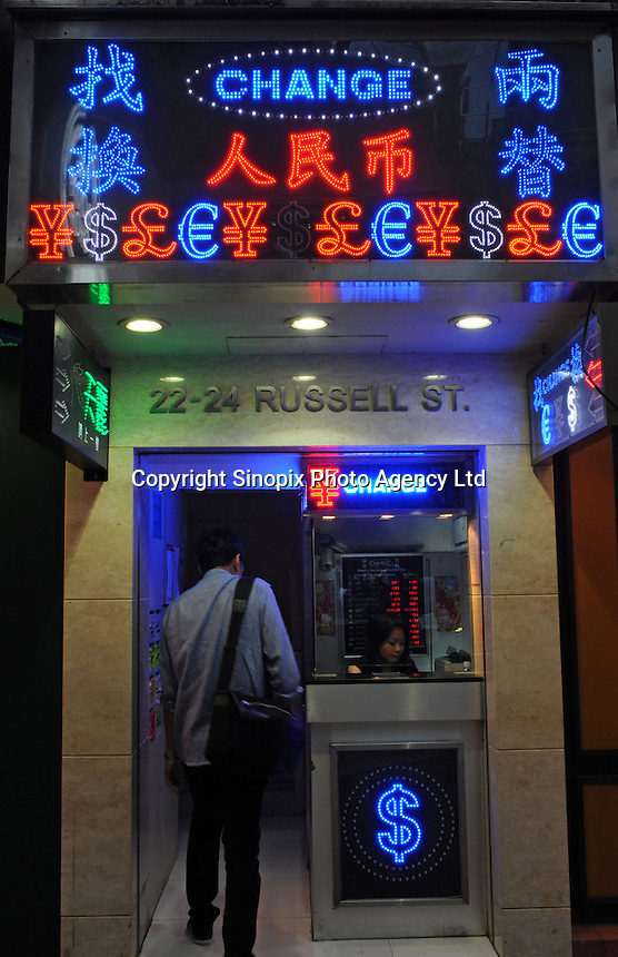 A passerby enters a money exchange shop, Hong Kong SAR, China. Hong Kong is a tax-free shopping paradise with hundreds of money exchange centres. For exchanging money, costs and fees will be assessed..