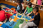 Education Preschool group of boys playing together with wooden train set