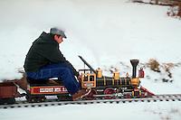 Model railroading - Man sits on a model train as it rides along tracks outdoors.