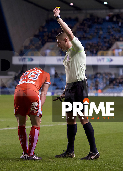 Liam Grimshaw of Chesterfield is shown the yellow card by Referee Robert Jones during the Sky Bet League 1 match between Millwall and Chesterfield at The Den, London, England on 21 February 2017. Photo by Alan  Stanford / PRiME Media Images.