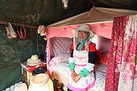 Luoping, Yunnan. A beekeeper in her tent, which is also her home for the eight months out of the year when the beekeepers travel from flowering field to flowering field.
