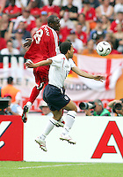 Cyd Gray of Trinidad leaps high over Aaron Lennon of England. England defeated Trinidad & Tobago 2-0 in their FIFA World Cup group B match at Franken-Stadion, Nuremberg, Germany, June 15 2006.
