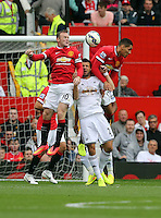 Pictured: Jordi Amat of Swansea (C) is squashed between Wayne Rooney (L) and Chris Smalling (R) of Manchester United. Saturday 16 August 2014<br />