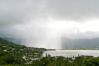 Dark storm clouds burst open with pouring rain and wind near the Koolau mountains(background) and Kaneohe Bay on Oahus windward side.