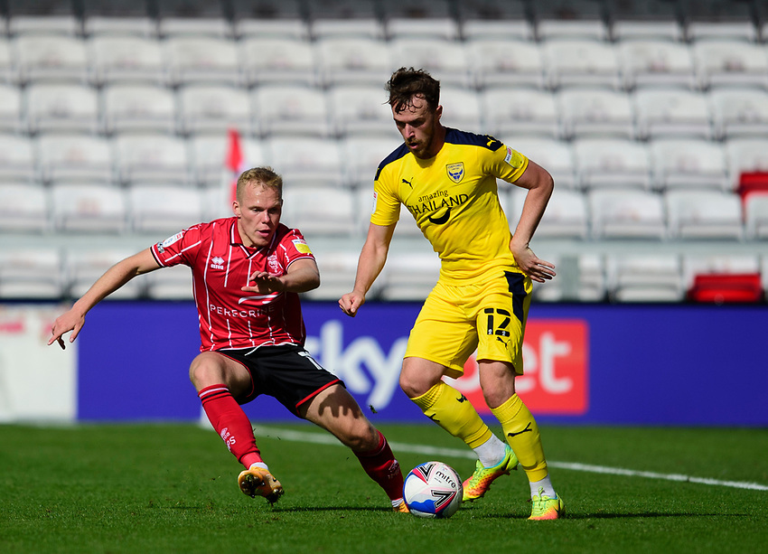 Oxford United's Sam Long shields the ball from Lincoln City's Anthony Scully<br /> <br /> Photographer Andrew Vaughan/CameraSport<br /> <br /> The EFL Sky Bet League One - Saturday 12th September  2020 - Lincoln City v Oxford United - LNER Stadium - Lincoln<br /> <br /> World Copyright © 2020 CameraSport. All rights reserved. 43 Linden Ave. Countesthorpe. Leicester. England. LE8 5PG - Tel: +44 (0) 116 277 4147 - admin@camerasport.com - www.camerasport.com - Lincoln City v Oxford United