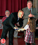 NAUGATUCK, CT-07 JANUARY 2009-010710JS01-Jasmine Braziel, 6, a first grader at St. Francis School in Naugatuck hands her father, former United States Marine Sgt. Kevin Braziel, with an American flag which he presented to principal Thomas Fuller, right, during a ceremony Thursday at the school. The flag flew over the United State embassy in Afghanistan. The flag was given as a token of gratuitude for donations the students collected for soldiers serving in Afghanistan.<br /> Jim Shannon Republican-American