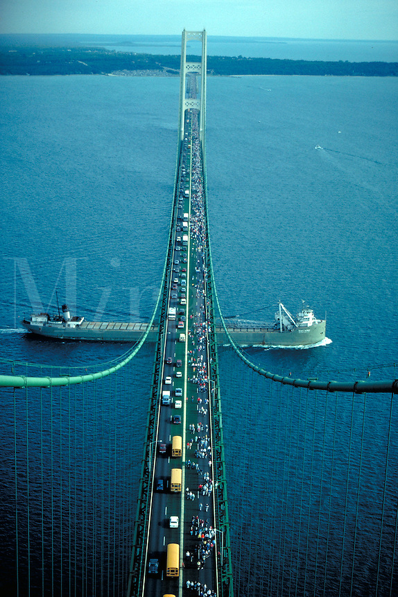 Freighter Irvin L. Clymer of USX Great Lakes fleet passing under bridge during annual Labor Day walk of approximately 70,000 participants, aerial, bridges. Mackinac Straits Michigan USA.