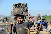 """MADAGASCAR Antananarivo, dumping site, people live from waste picking, catholic priest Per Pedro Opeka has build Akamasoa a social community project with housing schemes, health units and schools for ragpicker / MADAGASKAR Antananarivo , Muellsammler auf einer Muellkippe, Pater Pedro Opeka hat die Gemeinde Akamasoa , auf madagassisch """"gute Freunde"""" , mit Muellsammlern, Bettlern und Sozialschwachen auf einem Huegel bei Antananarivo erbaut, Teil des Projektes sind Hausbau, Schulen, Krankenhaeuser und Beschaeftigung"""