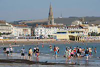 BNPS.co.uk (01202 558833)<br /> Pic: Graham Hunt/BNPS<br /> Date: 7th September 2021.<br /> <br /> Sunbathers flock to the beach to enjoy the scorching hot sunshine at the seaside resort of Weymouth in Dorset.<br /> <br /> Beachgoers paddle in the sea to cool off.