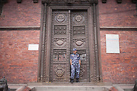A police man guards the entrance of an old structure in Kathmandu, Nepal