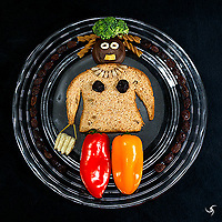 The last piece of bread in the loaf gave me the idea to create this photo: food items I had at that moment in the kitchen.<br /><br /> The Bread Lady Recipe:<br /> Hat: Broccoli<br /> Hair: Pasta<br /> Head: Chocolate Peanut Butter Cookie<br /> Eyes: Cereal<br /> Mouth: Onion Ring<br /> Body: Bread Slice<br /> Necklace: Sunflower Seeds<br /> Breasts: Dried Cranberry<br /> Purse: Spaghetti and Potato Chip<br /> Legs: Sweet Peppers<br /> Circle: Raisins
