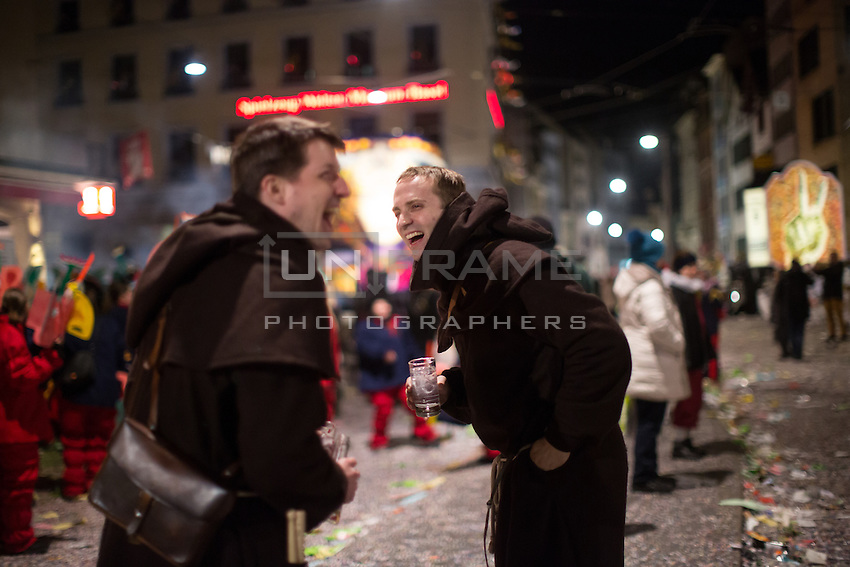 Two dressed up participants in Fasnacht, the Carnival of Basel, share a laugh as they drink on the last night of festivities in Basel, Switzerland. Feb. 26, 2015.