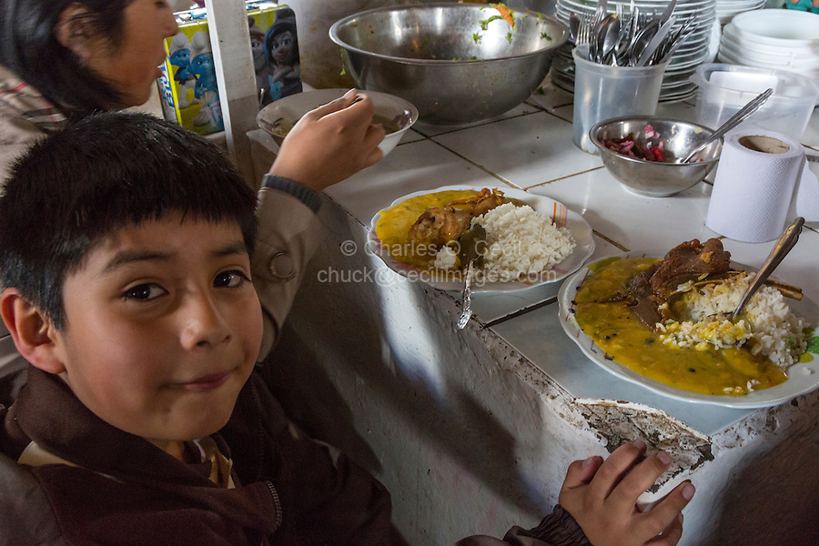 Peru, Cusco, San Pedro Market.  Young Boy with his Lunch of Rice, Beef, and sauce in the Food Court Area of the Market.