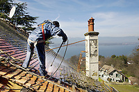 Switzerland. Geneva. A laborer from the company Cerutti Toitures SA is working on the maintenance of a private home's roof. The worker is using a water high-pressure cleaners to remove dirt and vegetation on slate tiles. Located in Cologny, the house has a view on Lake Geneva and the Jura mountains. 18.03.2014 © 2014 Didier Ruef