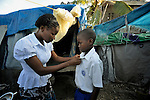 Roseline Sauveur helps Pierre Dawenson get dressed for school in a tent city in the Mais Gate neighborhood of Port-au-Prince, Haiti. More than a million survivors of Haiti's January 2010 earthquake continue living in temporary structures like these. The ten-year old boy is a student at the Notre Dame de Petits School, run by the Notre Dame de la Nativite Orthodox Church, a member congregation of the Russian Orthodox Church Outside of Russia.