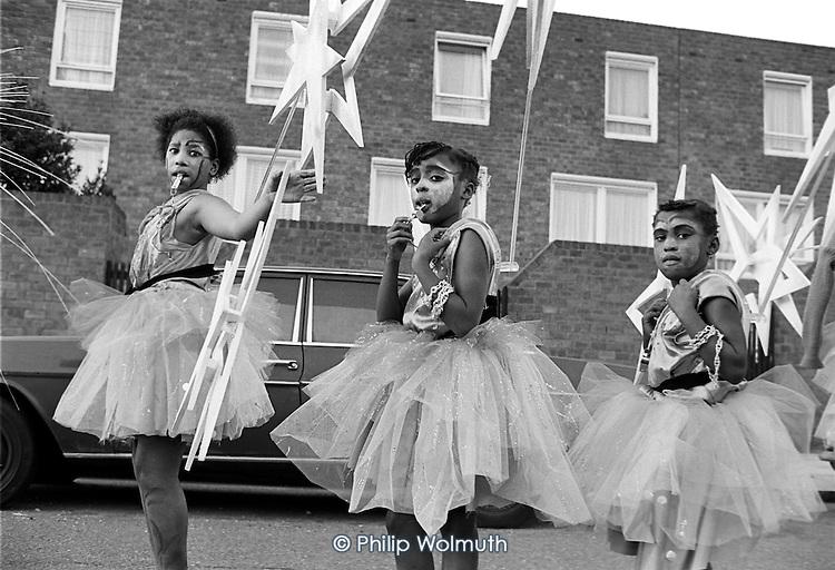 Flamboyan Mas Band wait to begin their parade along the Harrow Road.  Notting Hill Carnival Children's Day 1987.