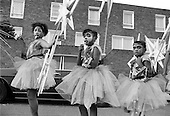 Flamboyan Mas Band wait to begin their parade along the Harrow Road.  Notting Hill Carnival Children's Day 1987.