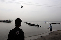 """A man looks out onto a beach in northern Jakarta. According to the Climate Reality Project, """"Without flood protection measures, sea level rise could expose up to 6 million Indonesians to annual coastal flooding. The worst of the flooding would occur on the island of Java, where Jakarta is located."""""""