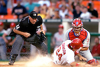 3 September 2005: Nick Johnson, first baseman for the Washington Nationals, is met by Philadelphia Phillies veteran catcher Todd Pratt, while home plate umpire Ed Montague watches carefully as the play unfolds. Johnson was out at the plate, but the Nationals defeated the Phillies 5-4 at RFK Stadium in Washington, DC. <br />
