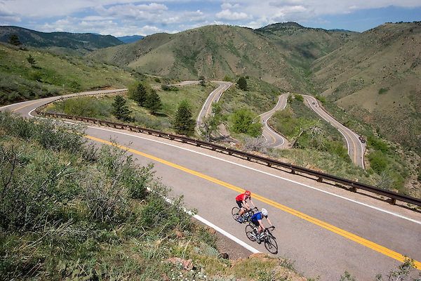 Men on road bikes riding up Lookout Mountain, Rocky Mountains near Denver, Colorado. .  John offers private photo tours in Denver, Boulder and throughout Colorado. Year-round.