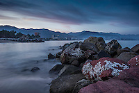 Fine Art Landscape Photograph of the early morning twilight and the misty ocean waves that were swirling around the rocks of this tranquil ocean bay in Puerto Vallarta, Mexico.