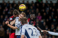 WEST BROMWICH, ENGLAND - FEBRUARY 11:  Craig Dawson of West Bromwich Albion  heads the ball away while Bafetibis Gomis of Swansea City  looks on during the Premier League match between West Bromwich Albion and Swansea City at The Hawthorns on February 11, 2015 in West Bromwich, England. (Photo by Athena Pictures/Getty Images)