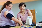 Elizabeth Welch checks the blood pressure of Rachel Parker at Westbourne Park Family Centre.