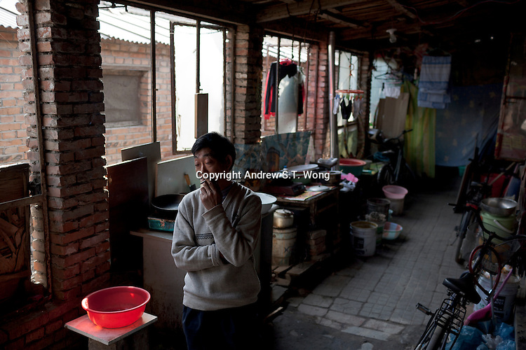 An elderly migrant worker from Sichuan Province smokes at his home at Dawangjing Village which is being demolished on April 9, 2009 on the outskirts of Beijing, China. The local authorities are evicting residents, who are mainly migrant workers, to redevelop the area. The redevelopment of Beijing continues in high speed.