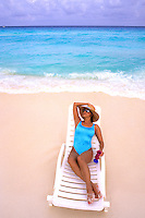 Young Hispanic woman on lounge chair on the beaches of Cancun Mexico.