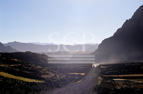Chivay, Peru. Road to Espinar with lorry raising dust on the dirt road in a blackened countryside.