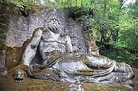 "Neptune,..The big statue of the seated Neptune... The big statue of the seated Neptune,The Park of the Monsters of Bomarzo.The Park of the Monsters  also named Sacred Wood is a Renaissance monumental complex located in Bomarzo, in the province of Viterbo, in northern Lazio, Italy.25 jun 2012..In the region of Lazio, the marvellous land of the Etruscans, the Romans and the Middle Ages, lies the village of Bomarzo which shares all the glory of the region's illustrious history and possesses an historical site which is the only one of its kind in the world: ""The Villa Of Marvels"". In the gardens of other villas in Lazio you will find certain similirities, but the prototype of all these gardens remains the ""Sacred Wood of Bomarzo"", that popular fancy rebaptized as Monster's Park. Prince Pier Francesco Orsini, known as Vicino, wanted such a park ""only to ease the heart"". It was designed and laid out by the great architect, Pirro Ligorio, who was summoned to work at Saint Peter's in Vaticano after the death of Michelangelo. Without either Prince Orsini or Ligorio ever realizing it, a timeless masterpiece was born. When you visit this park you will go from surprise to surprise as animals and figures in stone suddenly appear: the Elephant that is about to kill a Warrior, the fighting Dragons, the Ogre in whose mouth you could pic-nic, Sleeping Beauty, Hercules tearing Cacus apart, Bears in ambush, animals with three heads, Neptune presiding figures, and finally a globe of the world balanced on the head of an Orc with a model of the Orsini Castle on top representing the power of his family. These sculptures carred out of massive boulders in situ, appearing to rise up out of the very ground as if by magic. It all goes back to the 16th Century (1552), the period which saw the development of an ideal of life between Prince and Courtier. This wood has inspired many important artists and poets of the time such as Annibal Caro, Bitussi and Cardinal Madruzzo wanted to express their"