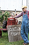 Farmer in front of his tractor that he will be auctioning off today