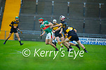 Crotta 's Darragh O'Donoghue slips past Michael Lenihan and Kevin Langers of Dr Crokes in the Senior County Hurling championship, round 2 game.