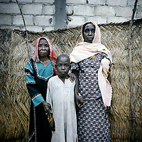 Ache Mal Ali, 80, with her daughter Amina Maloum Abba, 50 and her son Ali, 15 who is very small for his age. Chronic malnutrition has led to him being physically and mentally stunted.  <br /> <br /> Ache's village was attacked in the night and all the men in their family were taken away or killed. They now beg to try and gather enough for one meal a day, but sometimes even that is not possible. Following the attack they fled, walking for two months and taking refuge in villages along the way, until they reached Maroua where they have lived for over two years now, struggling to scrape together the rent for a small  single story house. Food is very scarce for this family. All the food is meticulously keep in small black plastic bags and tucked into holes in the wall. Every single bean is precious.  <br /> <br /> 'They attacked our village in the night. We heard the gunshots and we ran away. I was the oldest woman. We spent days and days with no food, just water to drink. That's how we survived. And it's how we survive now. I lost my husband. Two of my sons and my daughter's husband were lost.<br /> <br /> 'Before we lived in a good condition. We were farmers, it was a happy life. Since our village was attacked, it has been a nightmare. When we arrived here it was difficult. There was nowhere for us to stay. We spent weeks outside.<br /> <br /> 'We are afraid of not having enough. We don't think about the future. Food, water, somewhere to sleep. That's what we think about.<br /> <br /> 'It's very difficult. We try to get one meal a day, but it's difficult. It's a peaceful place. We are not attacked, but conditions are very difficult.<br /> <br /> 'The children have to go out and ask for help, for food or money. Most of the time they come back with rice. We can only eat one meal a day. We spend a lot of nights without eating. The children get sick. One of the children (Ali) is sick at the moment. It's not easy to think about our situation. I don't have a choice. We have to send children out onto the street for food. But we have no choice.<br /> <br />