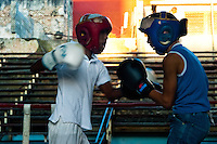 Young Cuban boys during a heavy training match at Rafael Trejo boxing gym in Havana, Cuba, 13 February 2010. During the last 30 years Cuba has produced more World Champions and Olympic gold medallists in amateur boxing than any other country. Many famous fighters, who came out of Cuba, were training at Rafael Trejo boxing gym in their youth. This run down open air facility in the Old Havana is a place of learning and mastering the art of boxing by the old school style. Boys begin their training very young. As sports are given a high political priority in Cuba, all children are systematically encouraged to develop their skills. Those who succeed will become heroes of Cuban society.