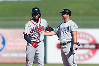 Peoria Javelinas center fielder Cristian Pache (27), of the Atlanta Braves organization, jokes around with hitting coach Doug Banks (14) after hitting a single during an Arizona Fall League game against the Surprise Saguaros at Surprise Stadium on October 17, 2018 in Surprise, Arizona. (Zachary Lucy/Four Seam Images)