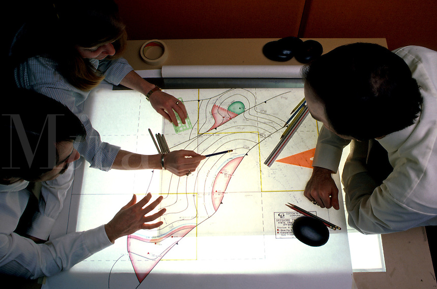 One adult female, two adult males, viewing geological seismic charts on light box. One adult female, two adult males. Houston Texas.