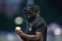 Home plate umpire Tre Jester checks a baseball during the game between the Charleston RiverDogs and the Kannapolis Cannon Ballers at Atrium Health Ballpark on June 29, 2021 in Kannapolis, North Carolina. (Brian Westerholt/Four Seam Images)