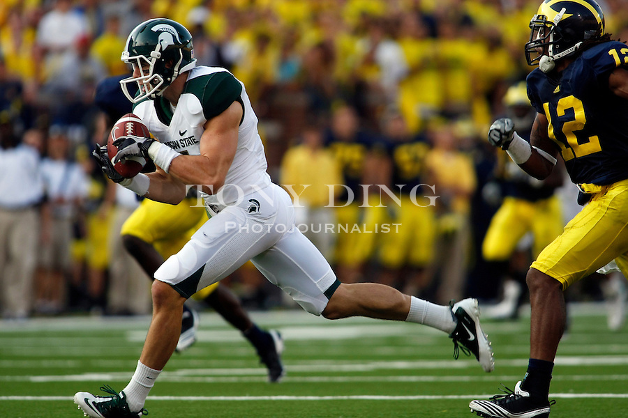 Michigan State wide receiver Keith Nichol (7) catches a 42 yard pass, pursued by Michigan cornerback J.T. Floyd (12), in the third quarter of an NCAA college football game, Saturday, Oct. 9, 2010, in Ann Arbor. Michigan State won 34-17. (AP Photo/Tony Ding)
