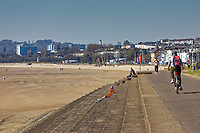 Pictured: People observe social distancing rules while enjoying the sunshine by the beach in Swansea, Wales, UK. Thursday 26 March 2020<br /> Re: Covid-19 Coronavirus pandemic, UK.