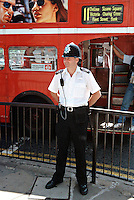 Police officer on foot patrol in central London. A red London bus can be seen in the background. This image may only be used to portray the subject in a positive manner..©shoutpictures.com..john@shoutpictures.com
