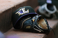 A Louisville Bats cap rests on a glove in the visitors dugout at Knights Stadium June 23, 2009 in Fort Mill, South Carolina. (Photo by Brian Westerholt / Four Seam Images)