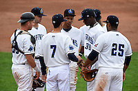 Lake County Captains manager Mark Budzinski (7) hands the ball to pitcher Alexis Paredes (30) during a pitching change as Richard Stock (28), Paul Hendrix (8), Ivan Castillo (9), Claudio Bautista (10) and Nellie Rodriguez (25) look on during a game against the Dayton Dragons on June 8, 2014 at Classic Park in Eastlake, Ohio.  Lake County defeated Dayton 4-2.  (Mike Janes/Four Seam Images)