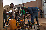 "AGADEZ, NIGER — <br /> Migrants, housed in what is commonly referred to as a ""ghetto"", fill up their water containers as they prepare for night fall before packing their belongings on the small pick-up trucks that will drive them through the desert on their way to Libya. Each migrant carries two gallons of water for the three day journey through the Sahara desert."
