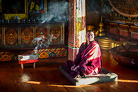 Chief monk at Gangtey Goemba during early morning prayer session, Gangtey, Bhutan