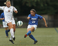 Duke University forward Mollie Pathman (24) crosses the ball as Boston College midfielder Gibby Wagner (10) closes.Boston College (white) defeated Duke University (blue/white), 4-1, at Newton Campus Field, on October 6, 2013.
