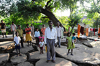 INDIA, Jharkand, Chaibasa, Ho tribe, fight for land rights, tribal villages and lands are threatened by mining and industrial projects, illegal land grabbing, displacement and resettlement are threatened, tribal villagers on grave slab of their ancestor under large tamrind tree, in case of resettlement the loose their connection with the ancestors and the land / INDIEN, Jharkhand , Chaibasa , Dorf Surjabasa , Ho Ureinwohner, Doerfer und Land der indischen Ureinwohner sind durch Bergbau und Industrieprojekte bedroht und es droht illegale Landnahme, Vertreibung und Umsiedlung, Dorfbewohner auf den Grabplatten ihrer Urahnen unter einem Tamarinden Baum, bei Umsiedlung droht der Verlust des kulturellem Erbes und die Verbindung zu den Ahnen und zum Land der Vorfahren